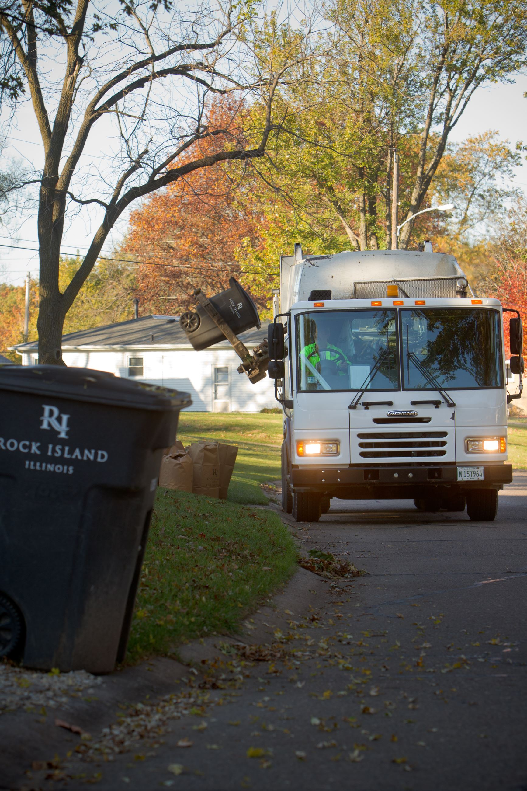 Refuse truck and cart in neighborhood during leaf bag collection
